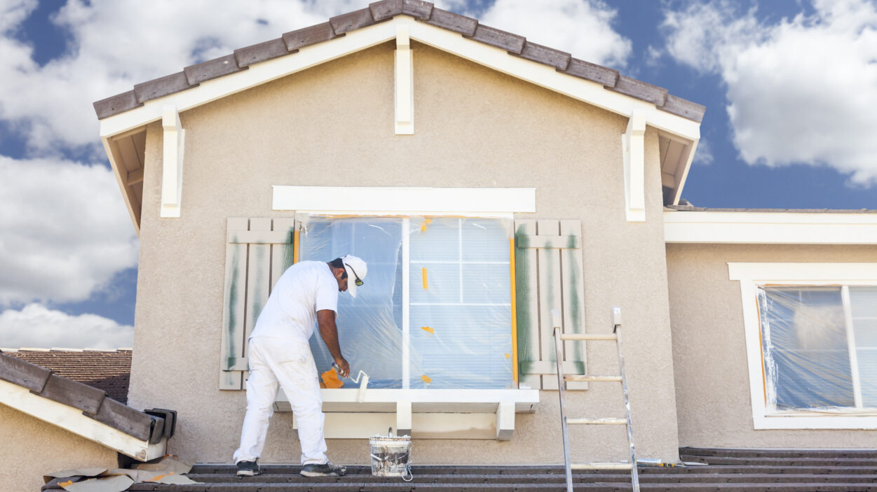 Man painting the outside of a home