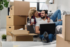 Young couple moving in new home.Sitting on floor and relaxing after unpacking.