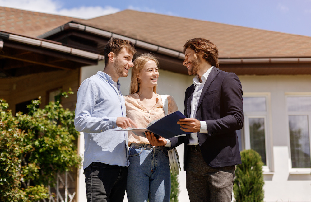 Showing home rental or purchase contract to his clients in house backyard
